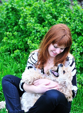 redheaded pretty girl playing with her dog on the meadow  photo
