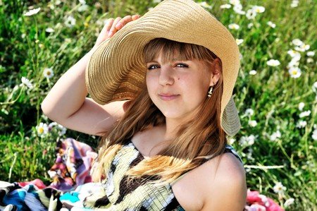 sweet teen girl wearing hat laying on the daisy meadow  photo