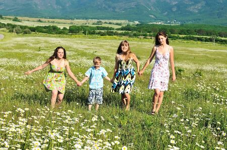 happy funny children and teens running in the daisy field  photo