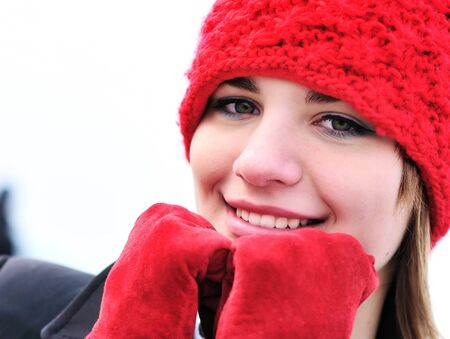 girl wearing reg hat and red gloves outdoors  photo