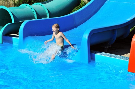Cute little boy sliding down a water slide to pool photo