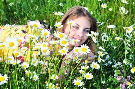 tender girl in daisy flowers on meadow  photo