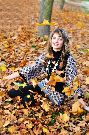 teen girl throwing leaves up in the autumn park photo