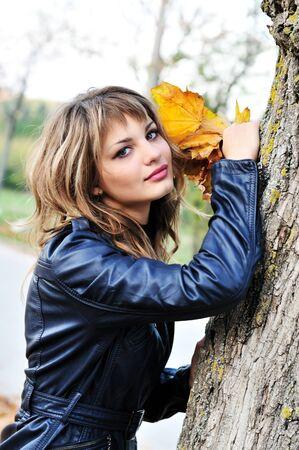 autumn teen girl standing near the tree photo