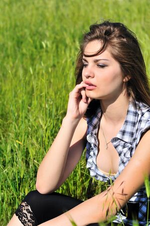spring beautiful teen girl sitting  on the meadow  photo