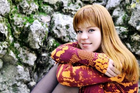 sitting redheaded young girl wearing orange dress photo