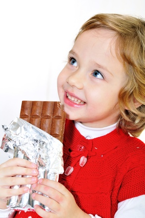 little pretty girl eating big chocolate bar photo