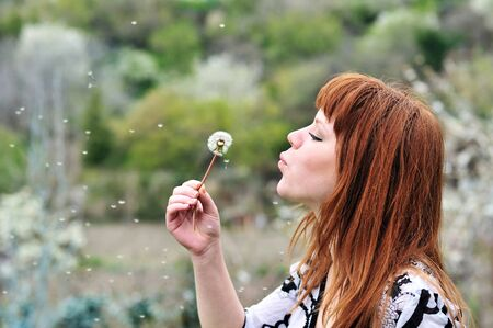 pretty redheaded teen girl blowing on dandelion  photo