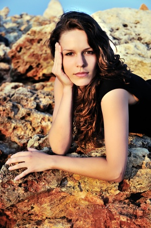 brunette girl laying on the cliff at sunset time photo