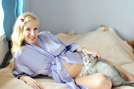 pregnant woman with her cat laying on the bed  photo