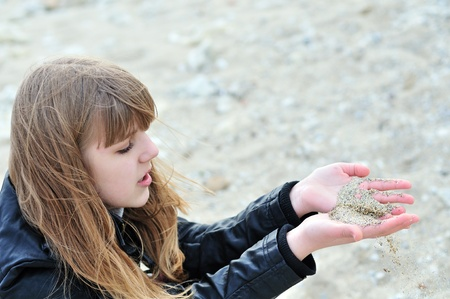 sand slips through  fingers of teenage girl Stock Photo - 8628829