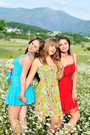 three happy teen girls standing in daisy field photo