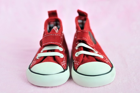 red baby shoes on pink background in soft selective focus photo