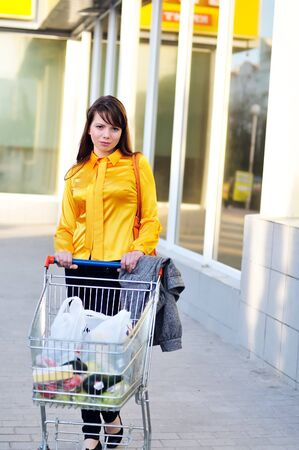 girl with shopping trolley going from shop to car  photo