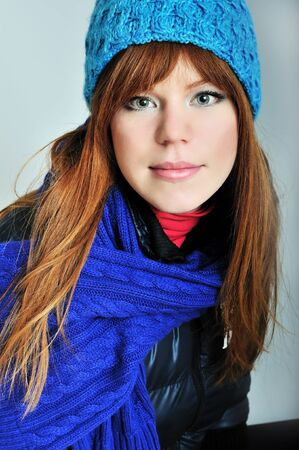 redheaded winter girl wearing blue scarf and hat photo