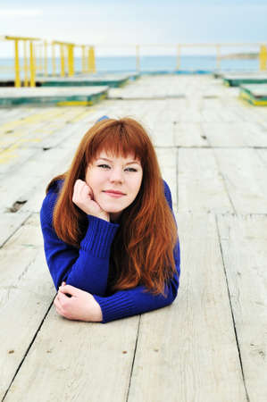 redheaded girl wearing blue clothes laying on the timber at spring time photo