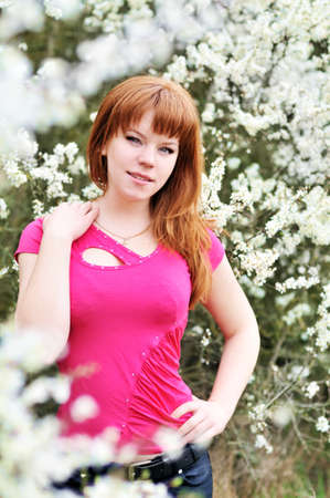 attractive redheaded girl standing in blossom garden  photo