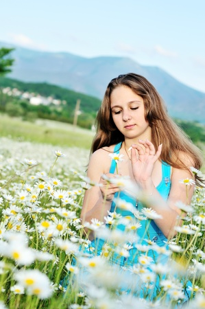 love sad: teen girl wondering about love on the petals of daisy flower