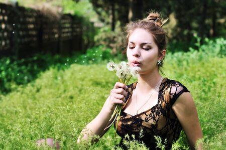 teen elegant pretty girl blowing on many dandelions  photo