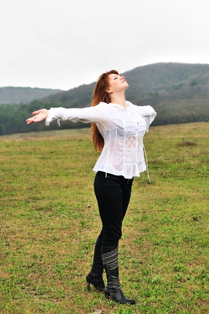 boughs: redheaded girl standing in field at one with nature, boughs reach out towards the rain