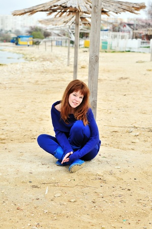 redheaded girl resting on the beach in spring time  photo