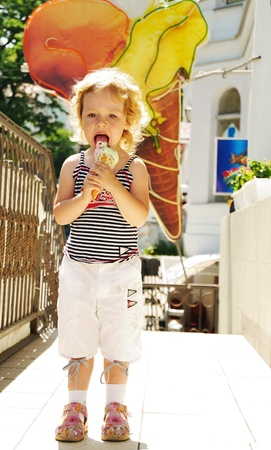 little funny blonde girl eating big ice cream  photo