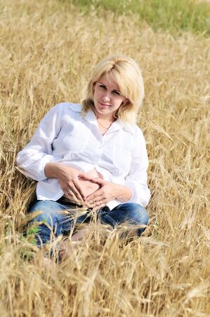haymow: blonde pregnant woman relaxing in the wheat field  Stock Photo