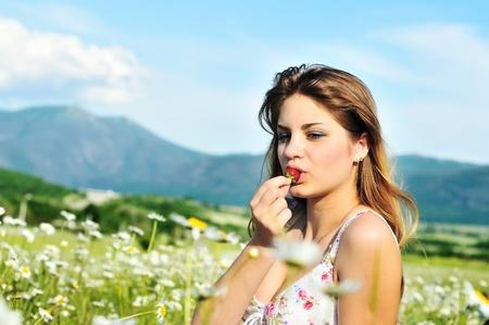 beautiful teen girl enjoying strawberry in daisy field  photo