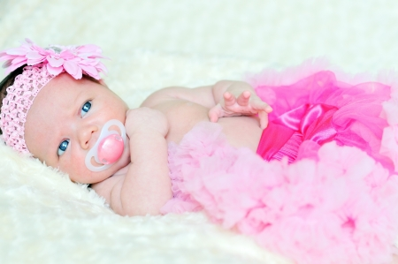 fashion newborn girl laying and wearing pink skirt Stock Photo - 14123836