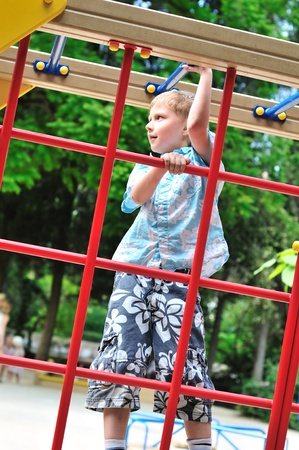 wall bars: boy climbing wall bars on the playground