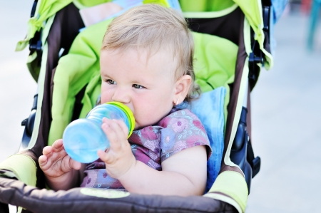 baby girl sitting in the stroller and drinking wate photo