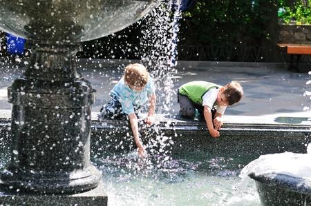 waterleiding: twee kleine jongens met plezier in de buurt van waterleidingbedrijf