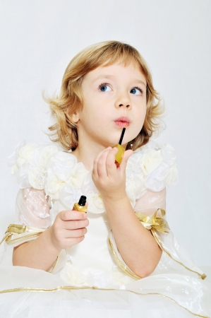 little funny blonde girl playing with lipstick  photo