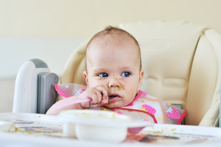 first meal of six months baby on her face and everywhere photo