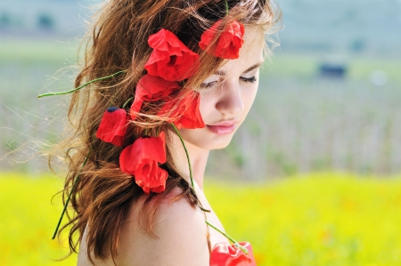 young lady standing with poppies in her hair photo