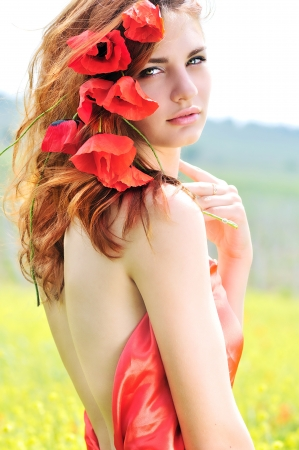 tender lady standing with poppies in her hair photo