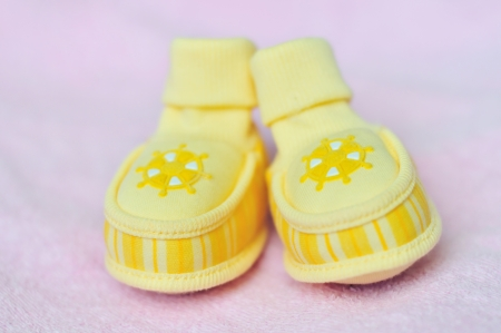 yellow little baby shoes in soft selective focus  photo
