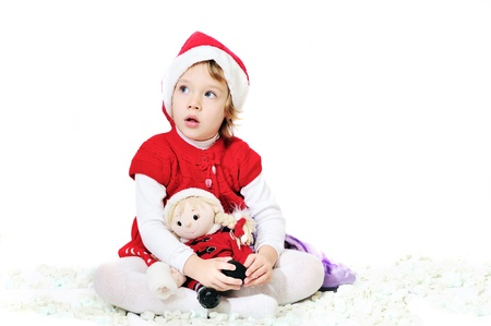 happy playing santa girl sitting with doll photo