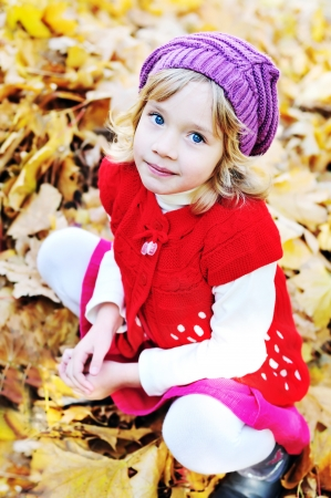 little blonde girl sitting in foliage photo