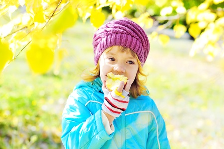 sweet little girl eating apple outdoors in fall time photo