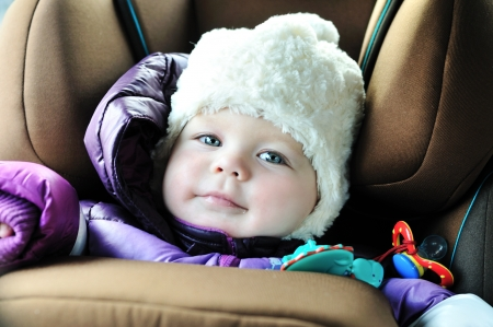 8 months old baby girl in a safety car seat with catch frame system Stock Photo