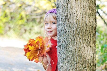 peekaboo: little girl with leaves in forest - Peekaboo! I see you!
