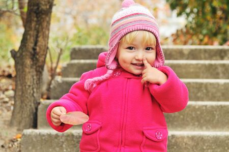 toddler girl pointing her nose and holding leaf photo