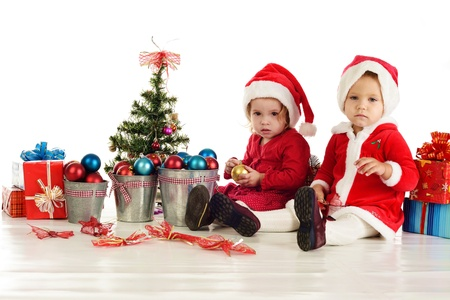 two serious santa girls sitting over the white Stock Photo - 18150120