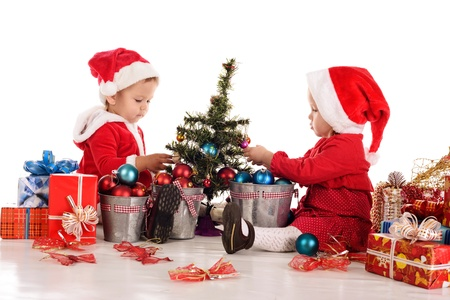 two  santa helpers decorating a tree photo