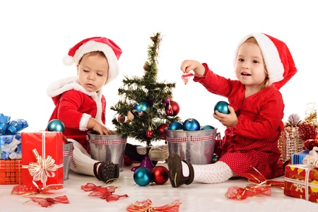 two sants girls decorating new year tree photo