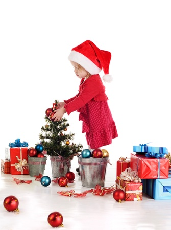 little santa helper decorating a tree over the white Stock Photo - 18150094