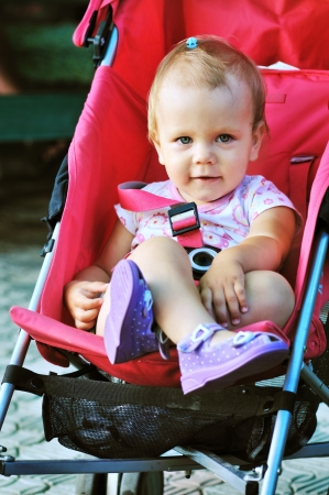 baby girl sitting in red stroller photo