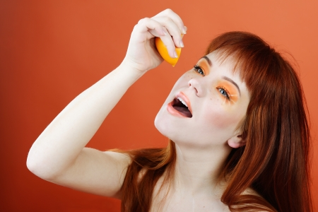 redheaded young woman enjoying of orange fresh juice photo
