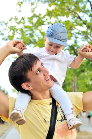 Young father with her daughter up on shoulders photo